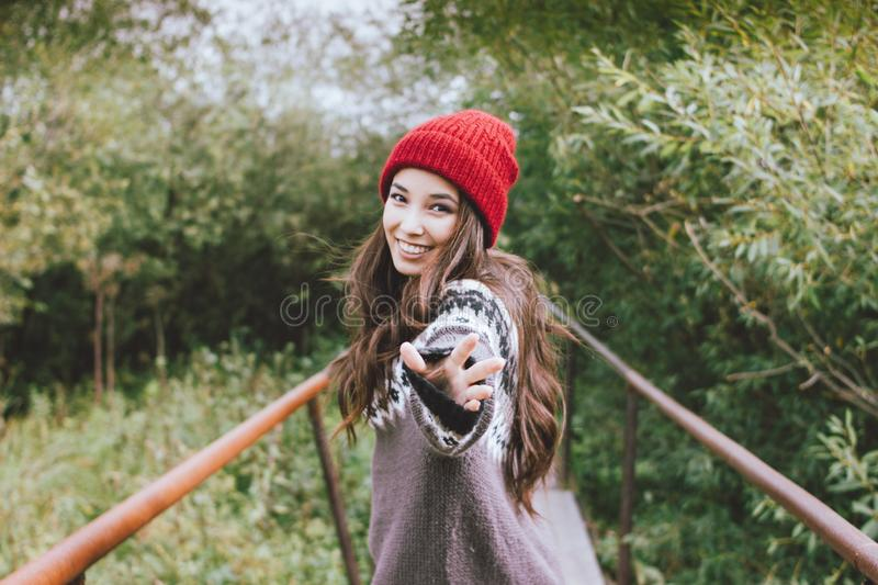 Beautiful carefree long hair asian girl in the red hat and knitted nordic sweater in autumn nature park, travel adventure stock images