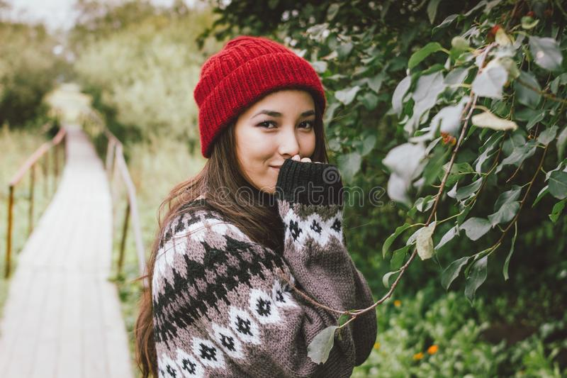 Beautiful carefree long hair asian girl in the red hat and knitted nordic sweater in autumn nature park, travel adventure royalty free stock images