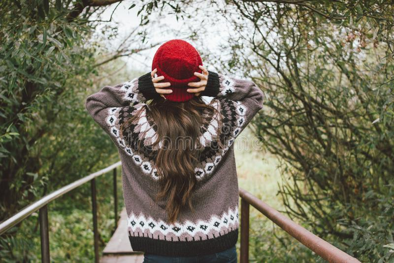 Beautiful carefree long hair asian girl in the red hat and knitted nordic sweater from behind in autumn nature park, travel stock photos