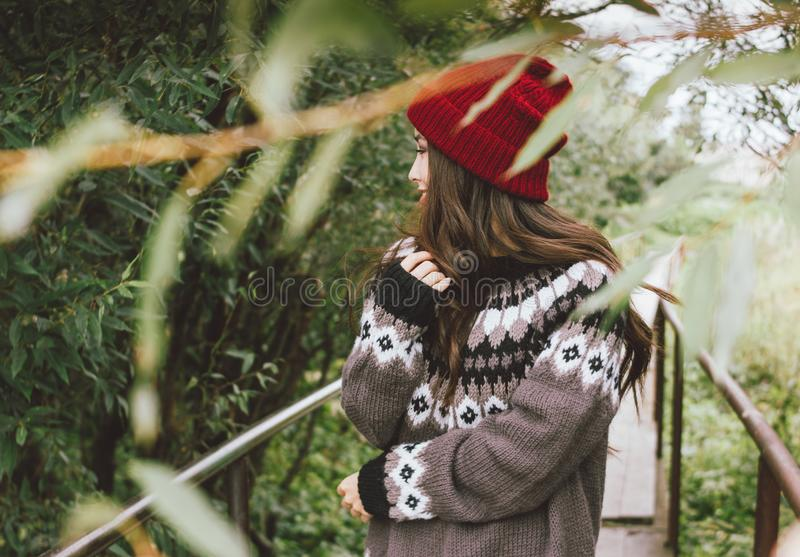 Beautiful carefree long hair asian girl in the red hat and knitted nordic sweater in autumn nature park, travel adventure royalty free stock image