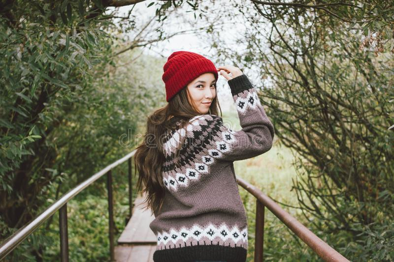 Beautiful carefree long hair asian girl in the red hat and knitted nordic sweater in autumn nature park, travel adventure stock photo