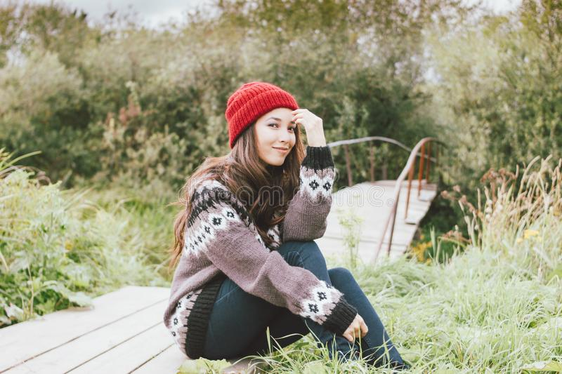 Beautiful carefree long hair asian girl in the red hat and knitted nordic sweater sitting in autumn nature park, travel adventure stock images