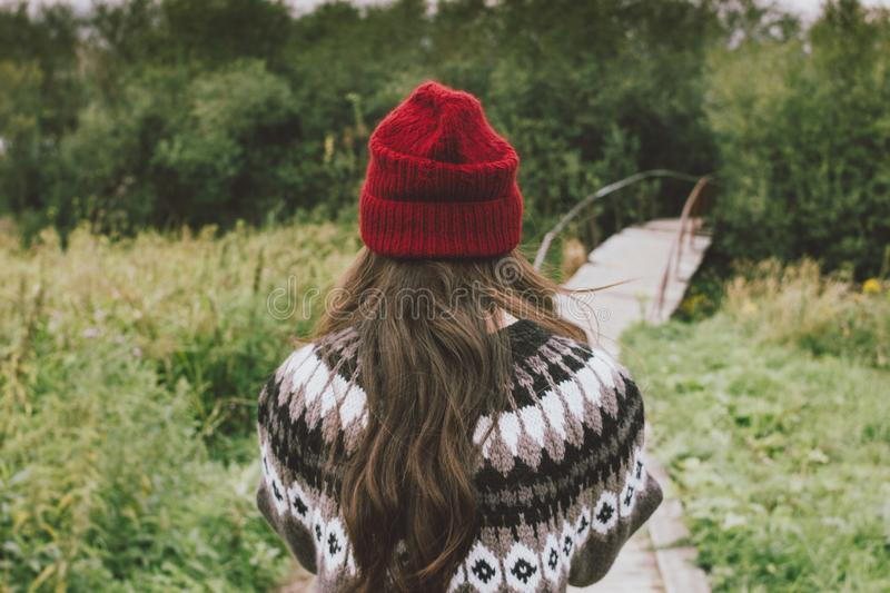 Beautiful carefree long hair girl in the red hat and knitted nordic sweater in autumn nature park, people from behind. Travel stock photo