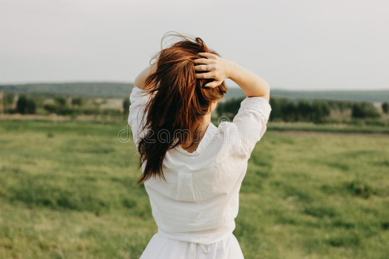 Beautiful carefree long hair girl in white clothes enjoys life in the nature field, view from back. Sensitivity to stock photography