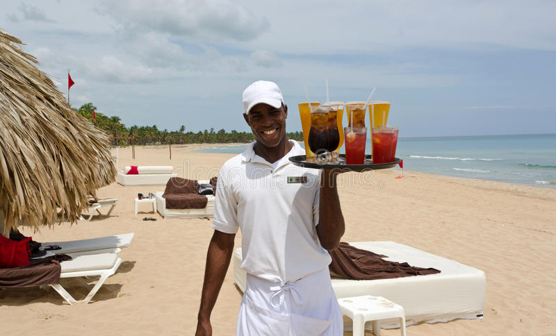 Beautiful Caribbean beach and local waiter royalty free stock photos