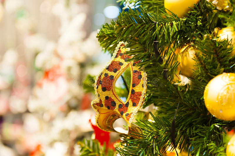 Beautiful carnival mask hanging on the Christmas tree in the background of bright Christmass decorations royalty free stock images
