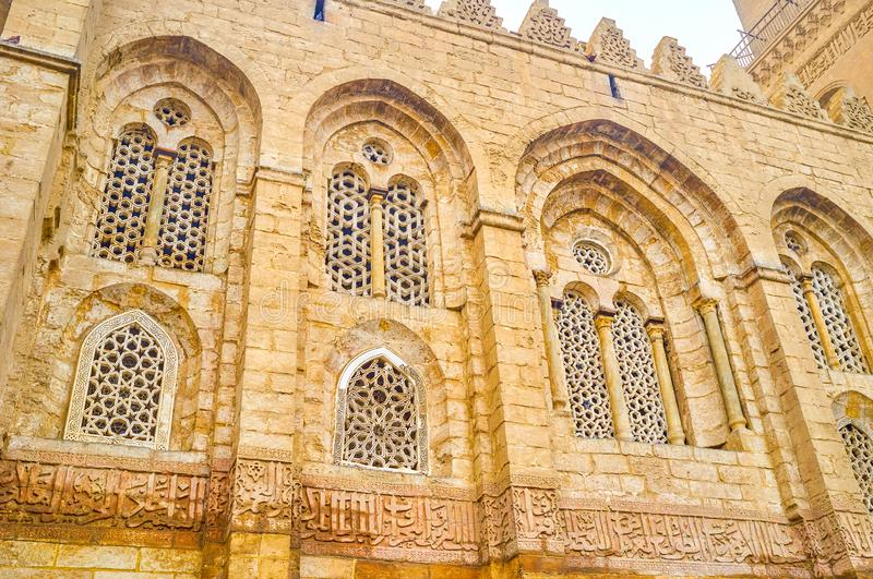 The stone arabian screen in medieval edifice in Cairo, Egypt. The beautiful carved arabian scereen loumted in the windows of Qalawun Complex in Cairo, Egypt royalty free stock photo