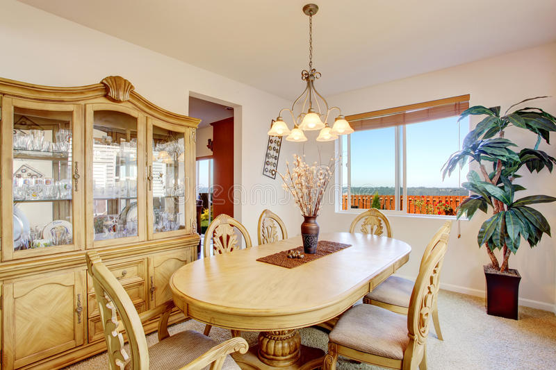 Beautiful carved wood dining table set in bright room. Bright dining room with rich carved wood table and chairs, cabinet and palm tree royalty free stock photography