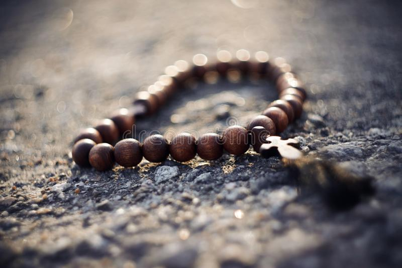 Wooden rosary lie on the surface, illuminated by God`s light royalty free stock images