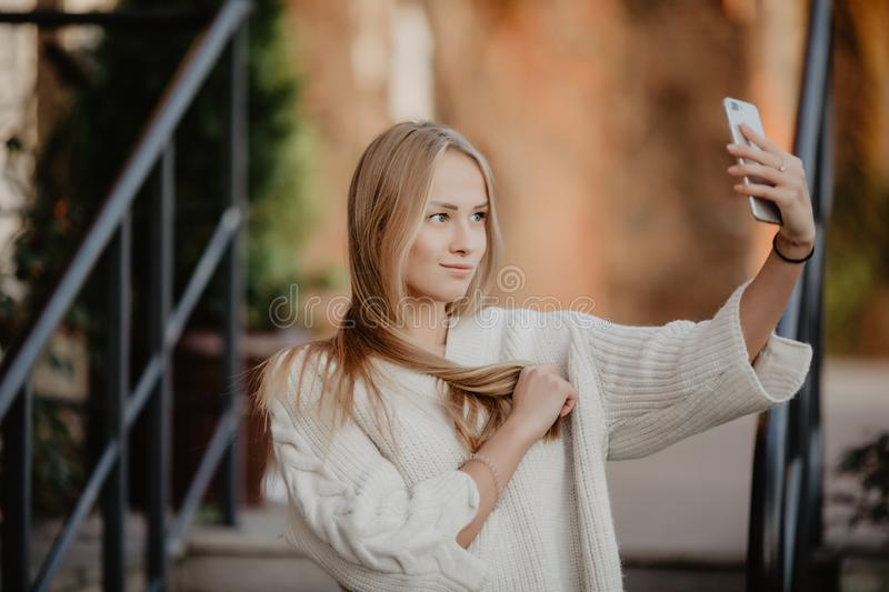 Beautiful casual blonde stylish fashion woman with a phone in her hand make selfie. European buildings and street on a background. Beautiful casual blonde royalty free stock image