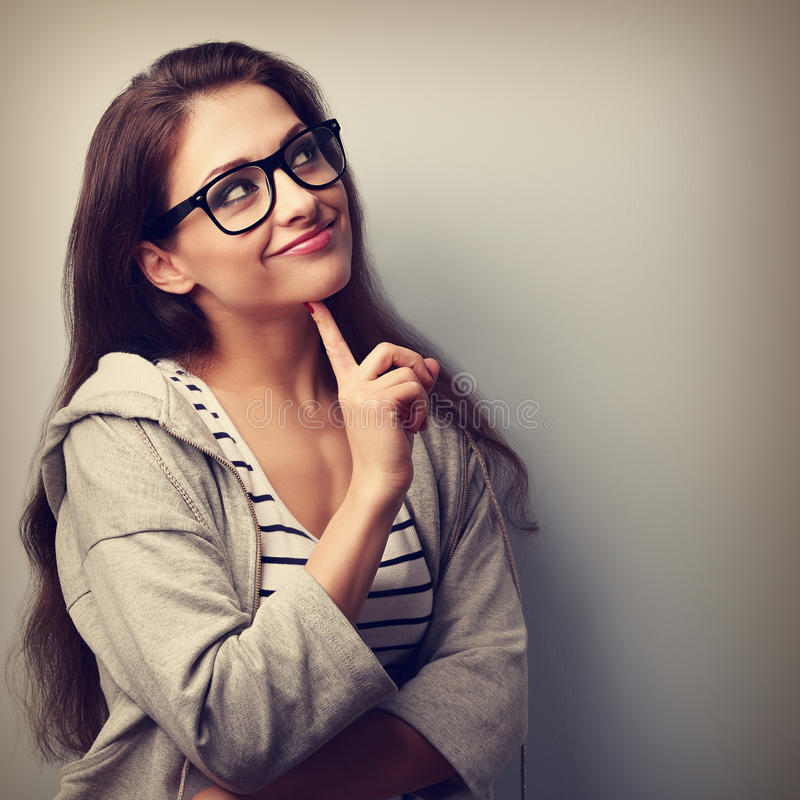 Beautiful casual thinking young woman in glasses looking up. Vintage portrait stock images