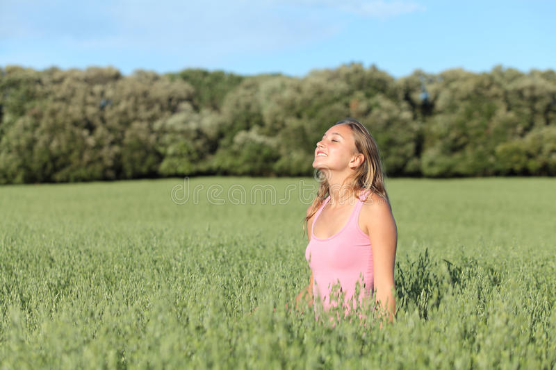 Beautiful casual woman breathing happy in a green meadow royalty free stock images