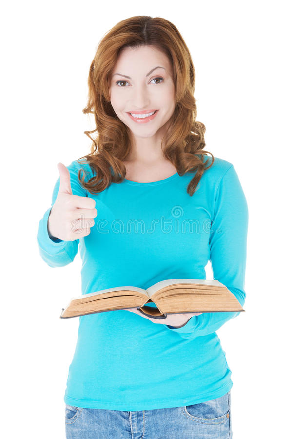 Beautiful casual woman holding a book and showing OK. stock photo