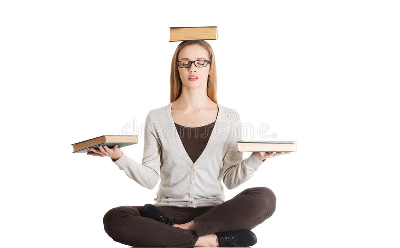 Beautiful casual woman sitting with books on palms and head, doing yoga. royalty free stock images