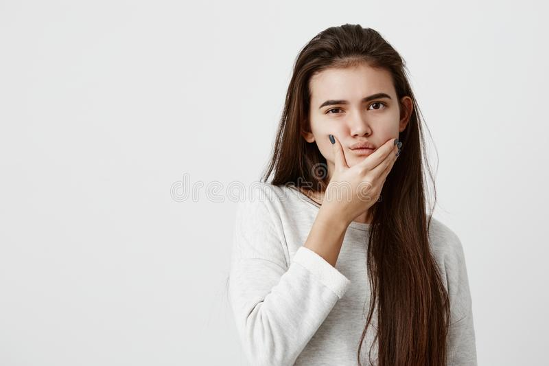 Beautiful casually dressed girl with long dark straight hair having doubtful expression, looking at camera with royalty free stock image