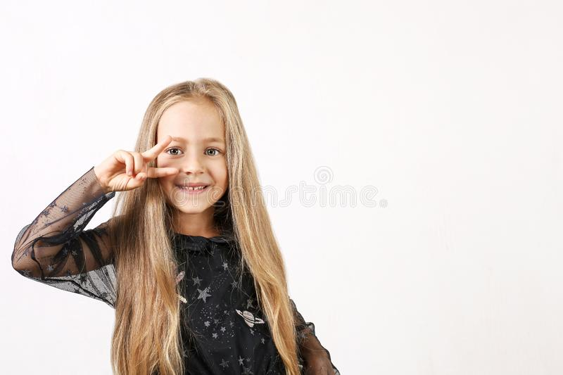 Beautiful caucasian blonde little girl in black dress with stars, white socks and shoes showing V sign victory gesture. Background royalty free stock images