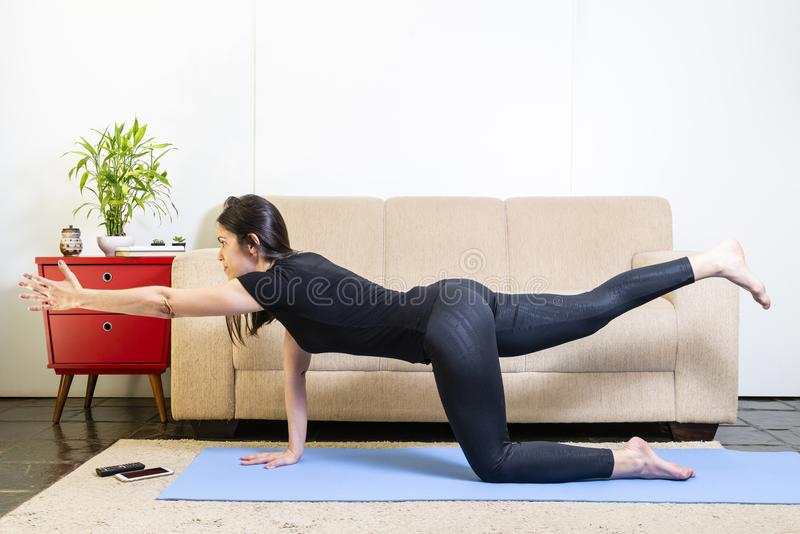 Beautiful caucasian brunette woman in black clothes on blue yoga royalty free stock photography
