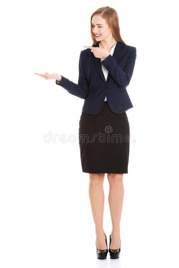 Beautiful caucasian business woman pointing on copy space on her side. royalty free stock photography