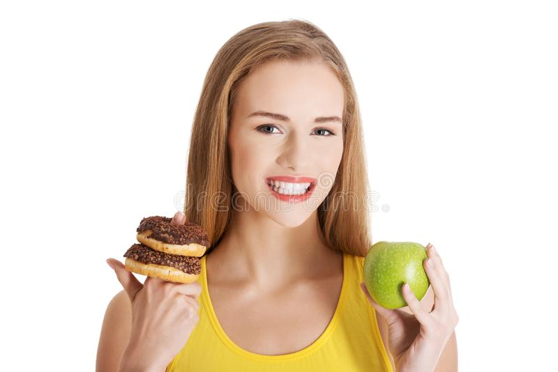 Beautiful caucasian casual woman with doughnuts and apple. stock photo