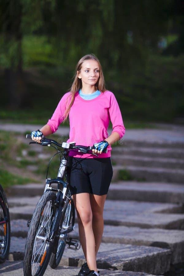 Beautiful Caucasian Female Biker with Mountain Bike Walking On S royalty free stock photos
