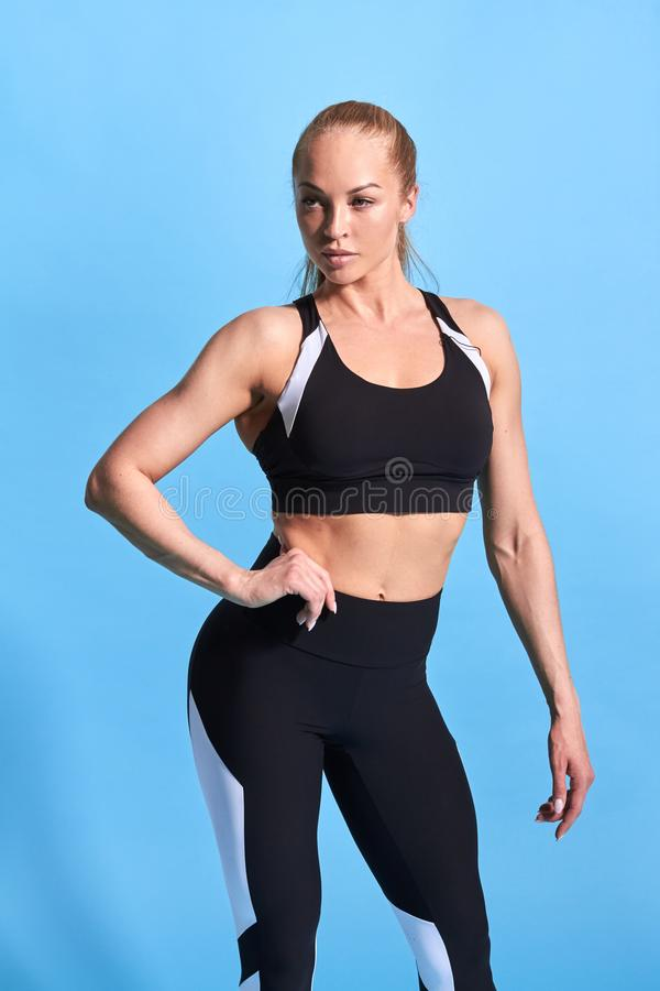 Beautiful Caucasian female bodybuilder with hands on hips standing at gym. royalty free stock image