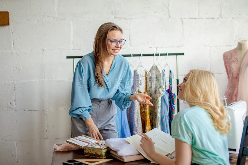 Female seamstress discussing features of the order with client in cozy studio stock photo