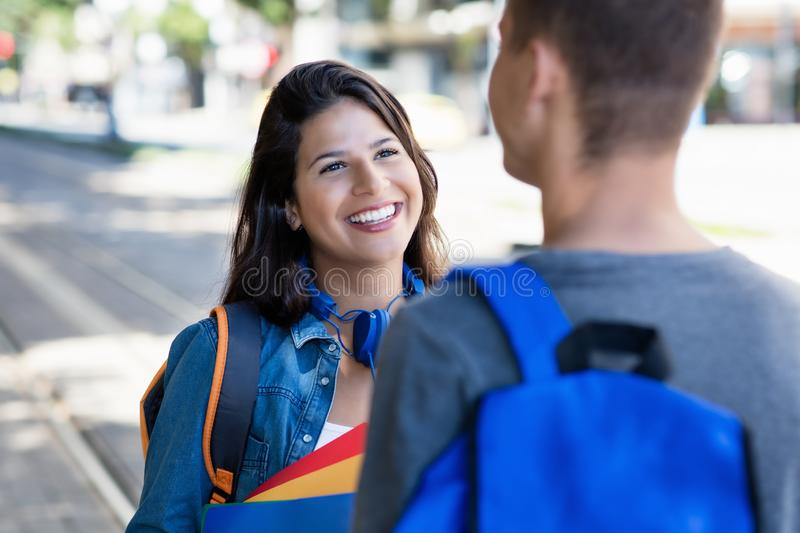 Beautiful caucasian female student talking with male student in city stock photos