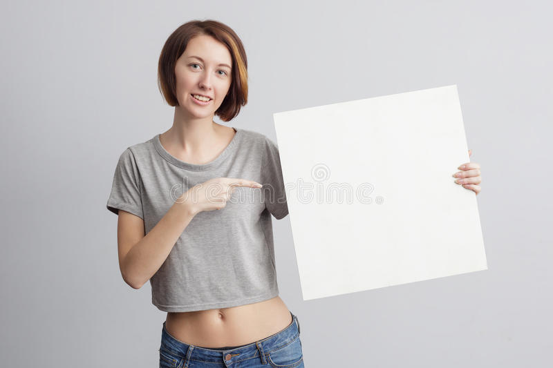 Beautiful caucasian girl holding a blank poster for text or ad. Beautiful caucasian girl in casual clothes holding a blank poster for text or ad stock photography