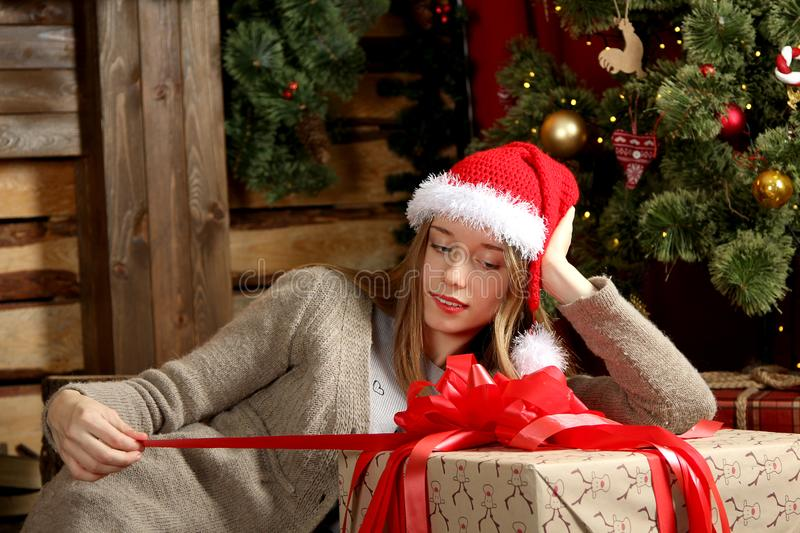 Girl opens big Christmas gift. Beautiful Caucasian girl in red hat opens big Christmas gift near Christmas tree in room stock photos