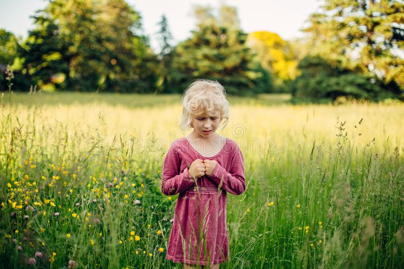 Beautiful Caucasian girl in tall grass on meadow at sunset. Little sad unhappy blonde Caucasian girl in tall high grass on meadow at sunset. Lonely feared royalty free stock images