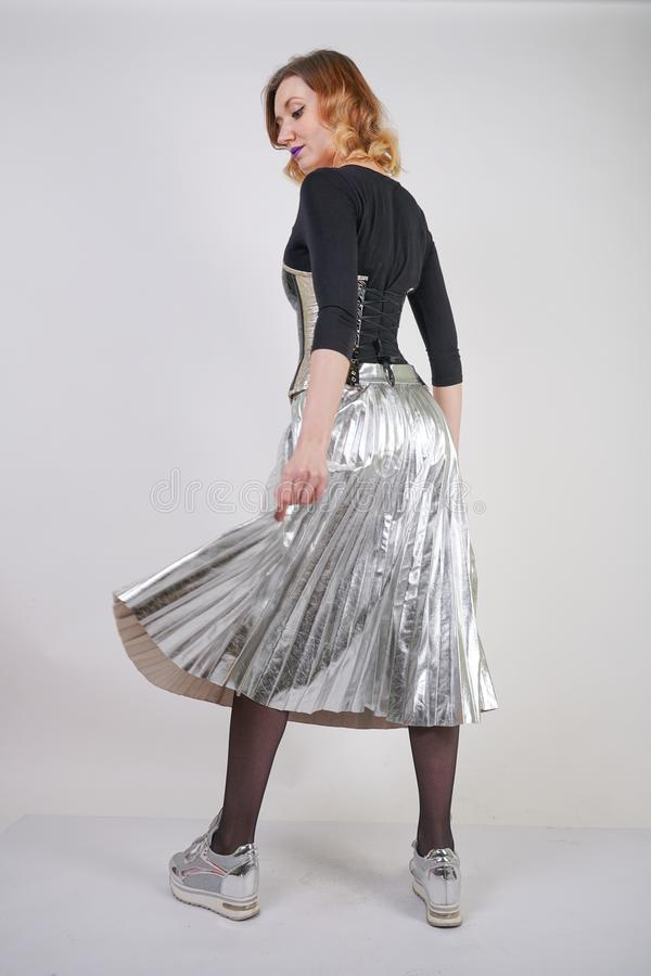 Beautiful caucasian girl wearing futuristic pvc corset and plaid metallic skirt with mirrored running shoes on white background in royalty free stock images