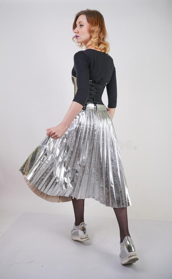 Beautiful caucasian girl wearing futuristic pvc corset and plaid metallic skirt with mirrored running shoes on white background in stock photos