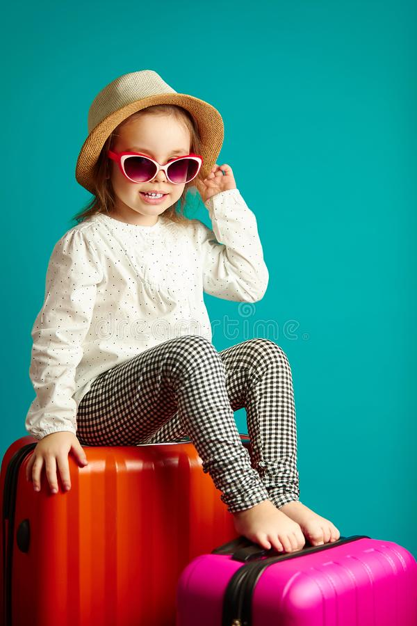 Beautiful caucasian little girl in beach hat and sunglasses sitting on suitcases over a blue isolated background, in stock images