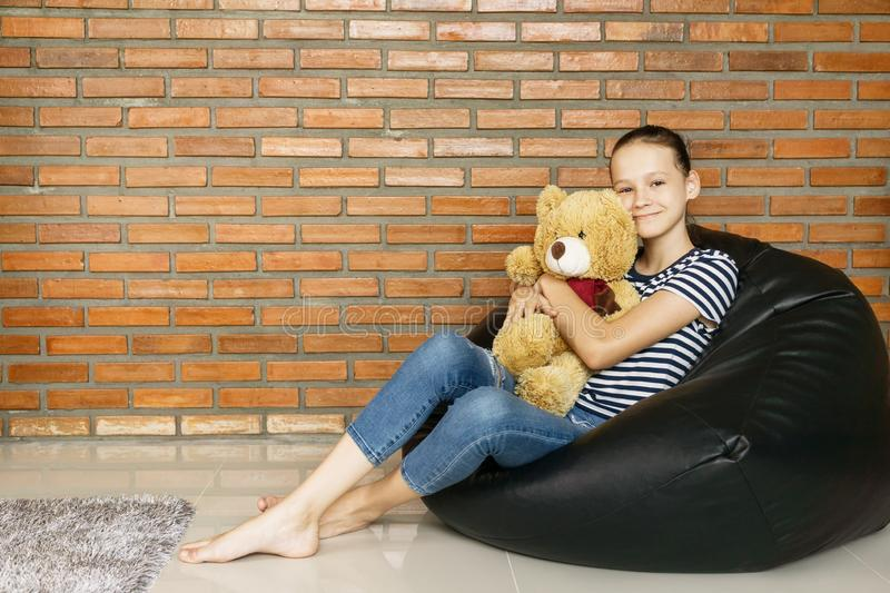 Beautiful caucasian teen girl sitting in black bean bag chair holding big brown teddy bear toy and smiling in camera. Casual outfi stock images