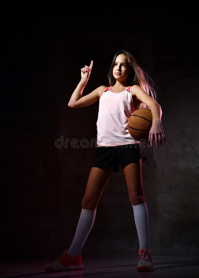 Beautiful caucasian teen woman in sportswear playing basketball . Sport concept isolated on black background. royalty free stock image