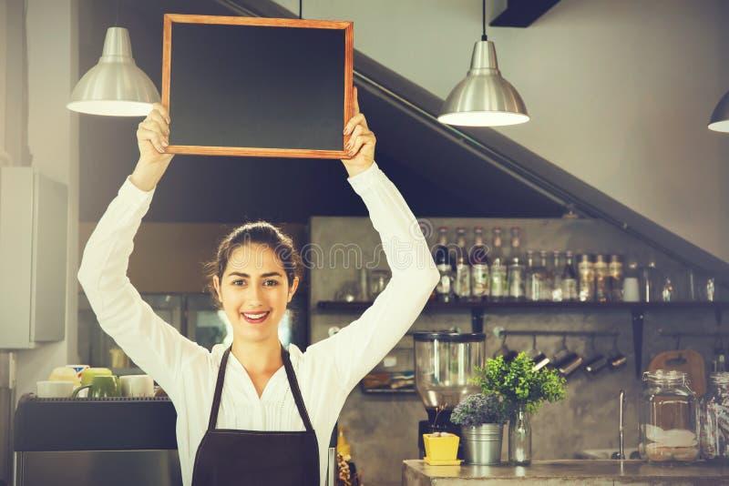 Beautiful Caucasian woman in barista apron holding empty blackboard sign inside coffee shop royalty free stock photography