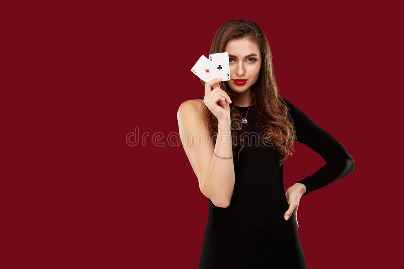 Beautiful caucasian woman in black dress with poker cards gambling in casino royalty free stock photography