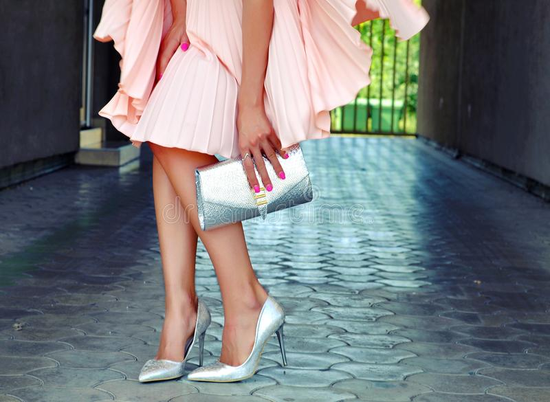 Beautiful Caucasian woman in elegant romantic fluttering dress, wearing silver high heels and holding handbag. royalty free stock images
