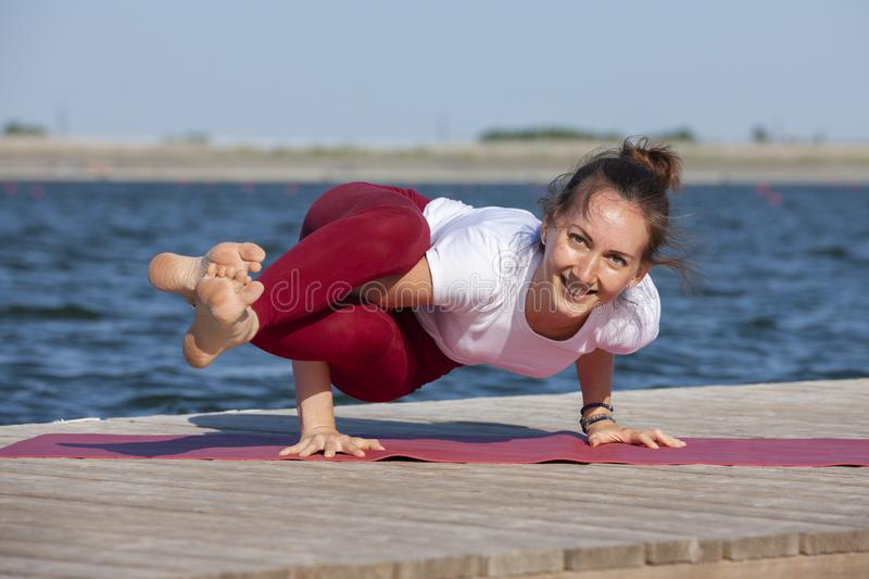 Beautiful caucasian woman exercising yoga in nature next to a lake. Portrait royalty free stock photos