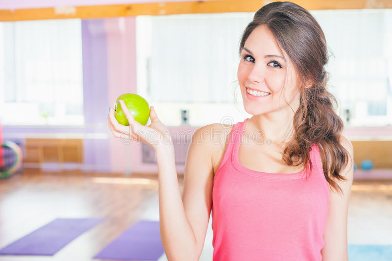 Beautiful caucasian woman after fitness exercise holding green aple. Eating, sport and healthy lifestyle concept royalty free stock images