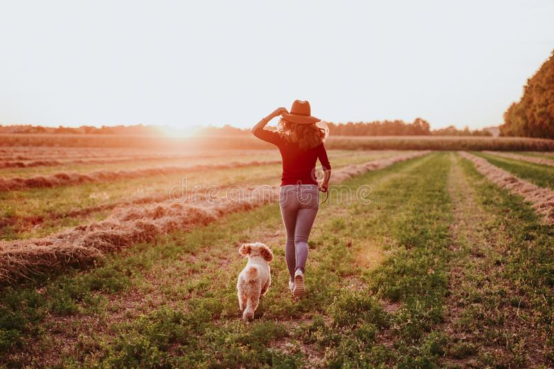beautiful caucasian woman with her cute brown poodle dog at sunset in countryside. Pets and lifestyle outdoors royalty free stock image