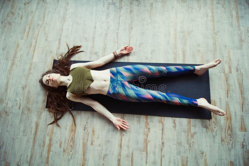 Beautiful woman in yoga class. Beautiful caucasian woman with long hair and slender body doing yoga on a mat top view ,leisure and relaxation in shavasana stock photos