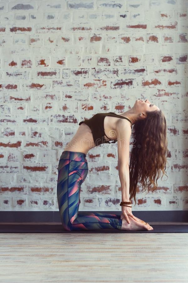 Beautiful woman in yoga class. Beautiful caucasian woman with long hair and slender body doing yoga in yoga class, ushtrasana yoga pose royalty free stock image