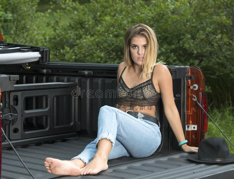 Beautiful Caucasian woman poses in bed of truck. Young Caucasian woman poses in the back of a pick up truck - country girl stock photo