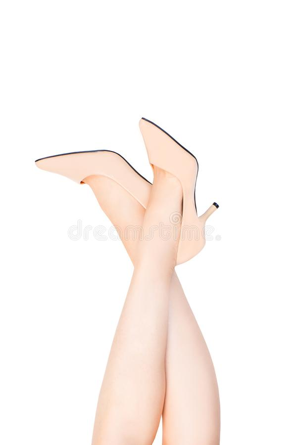 Beautiful Caucasian Woman Legs Wearing Beige Medium High-Heels Shoes on White Color. Fashion Accessory Shoe Selfie. Female. Wear Nude Sandals on White Studio royalty free stock photo