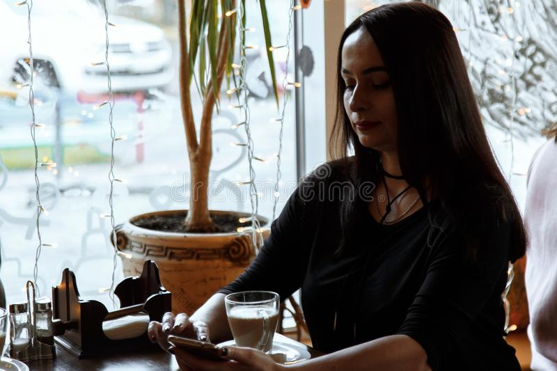 Beautiful caucasian woman sitting at a wooden table in a cafe, browsing internet using phone. and drinking coffee. Silhouette in. Backlight from the window, low royalty free stock images