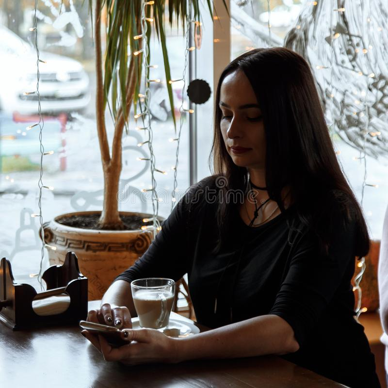 Beautiful caucasian woman sitting at a wooden table in a cafe, browsing internet using phone. and drinking coffee. Silhouette in. Backlight from the window, low royalty free stock photo