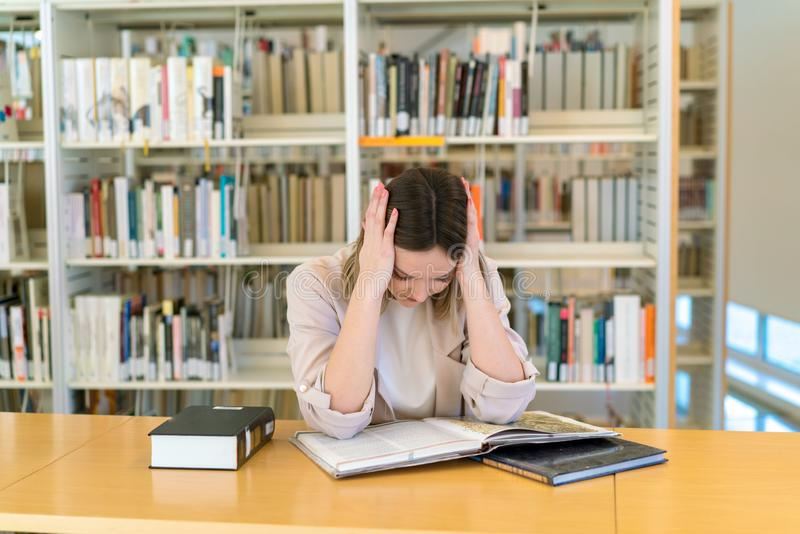 Beautiful caucasian young girl exhausted in the library royalty free stock images