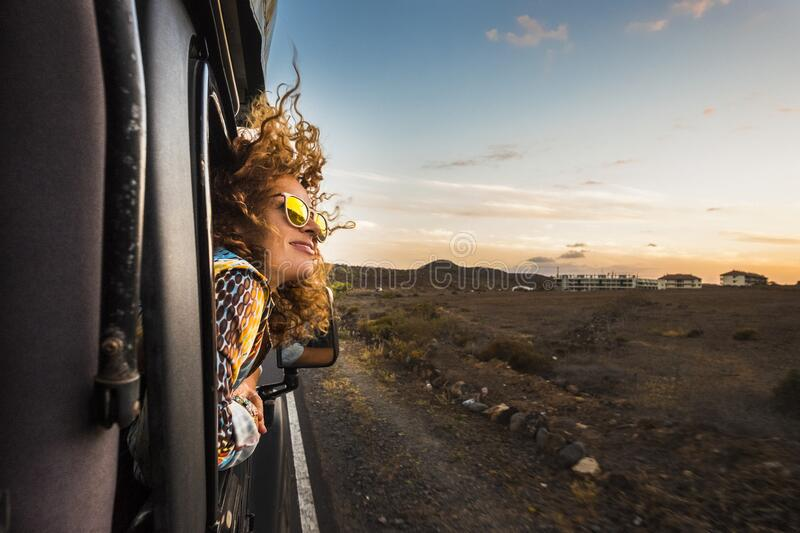 Beautiful caucasian young woman travel outside the car with wind in the curly hair, motion and movement on the road discovering royalty free stock photo
