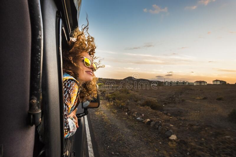 Beautiful caucasian young woman travel outside the car with wind in the curly hair, motion and movement on the road discovering stock images